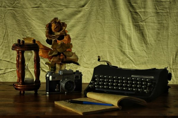 maszyna do pisania, notes, kwiaty w wazonie